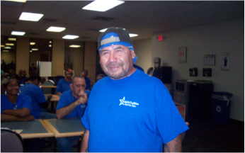 A man worker smiling at the camera in an office with other workers sitting at tables in the background