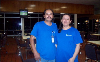 A man and woman worker standing together for a photo in an empty public space with tables and chairs in the background