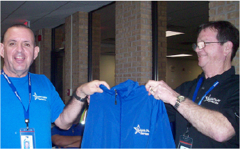 Two workers smiling in a photo together holding a Reliable Facilities Service Inc. jacket